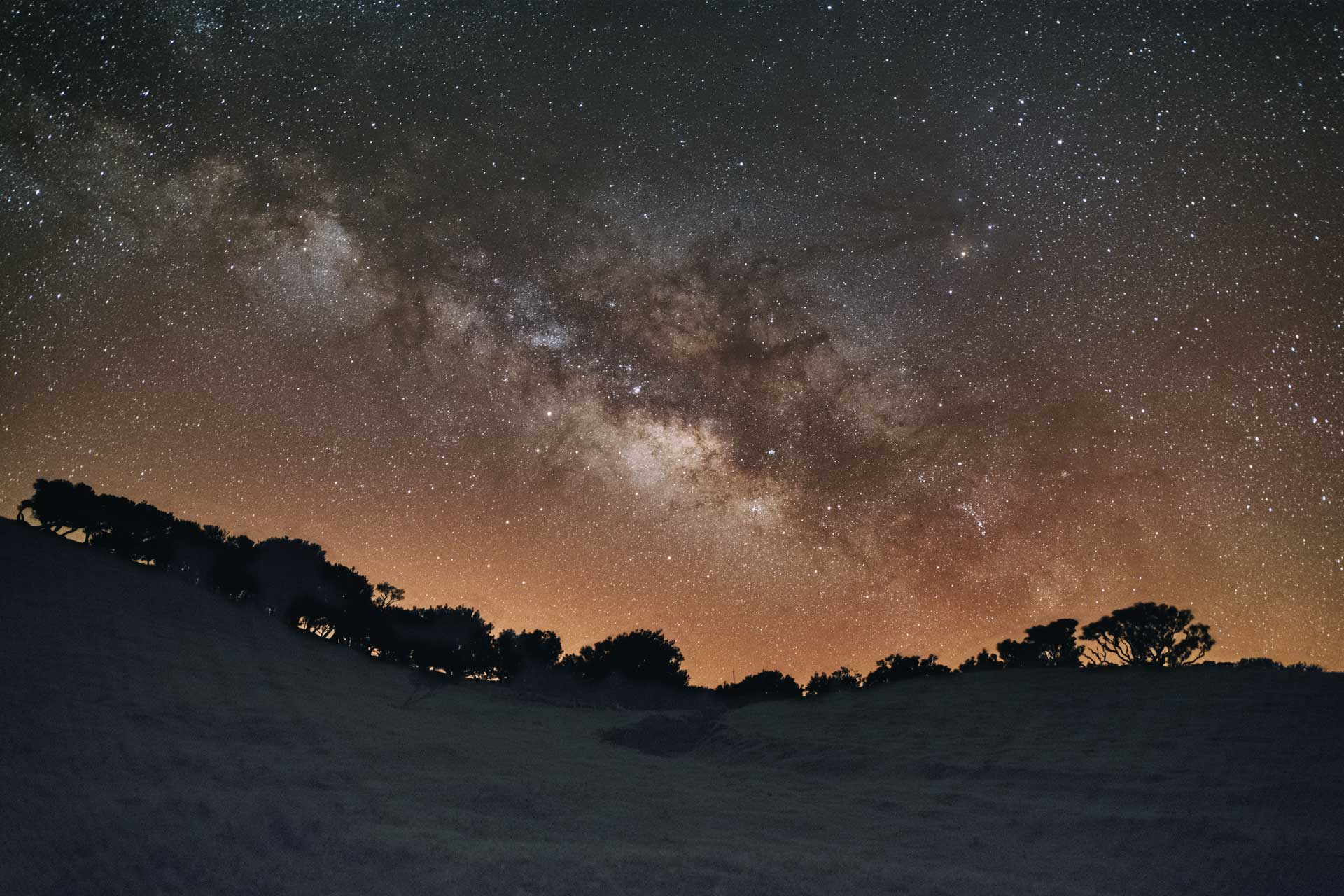 Milky Way Galaxy over hills with trees