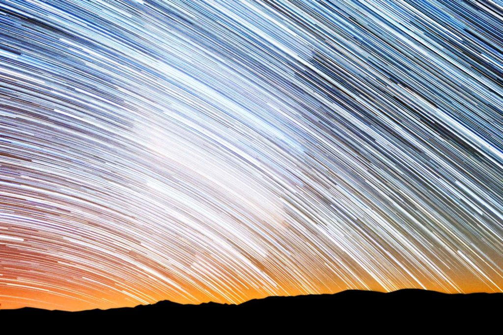 Star trails over mountains